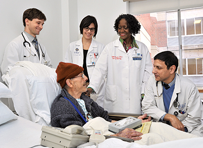 The team, whose meetings with patients are ongoing, consists of, from right, hospitalist Balal Ahmed, MBBS, Dr. Julietta Fiscella, and residents and students. Dr. Fiscella provides the team with mini reviews of staining, cellular structure, and other aspects of surgical pathology.