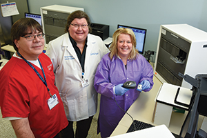 "Dr. Wolk (center) with Francis Tomashefski, BS, MT(ASCP), and Lisa Scicchitano, BS, MT(ASCP). Laboratories in the U.S. are often falsely labeled as cost centers, Dr. Wolk says, but she and colleagues see their lab as a ""cost recovery center,"" and they aim to prove it for every laboratory intervention they make."