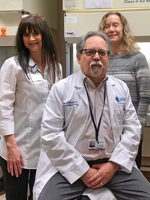 "Sherry Childress (left) and Dr. Gail Woods with Dr. José Romero at Arkansas Children's. ""I think everyone around the country has been surprised by the number of cases we're seeing,"" Dr. Romero says."