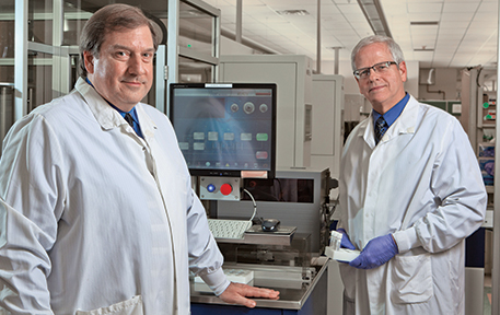 Kahn, left, and Clark at Alverno central laboratory, where the benefits of automation in terms of staff time have been seen already. Left: Canister from the unload stacker station of Copan WASPLab with plates that have been designated by digital image review to be removed from the incubator for transfer to a workstation to complete ID and susceptibility testing processing.