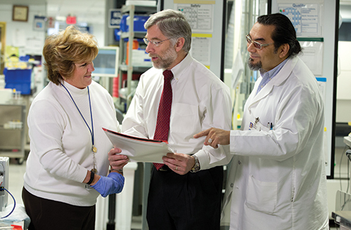 """John Waugh with Ruth Doubleday, lab systems analyst. and Ralph Benitez, supervisor of lab support services. Laboratories continue to get disproportionately hit by reimbursement cuts, Waugh says, because they are more of a """"back of the house"""" function."""