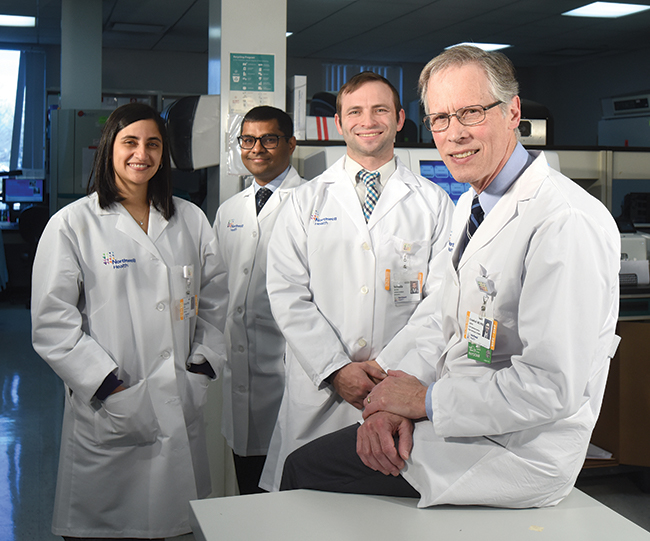"""Dr. James Crawford (right) with (from left) Reeti Khare, PhD, assistant director of infectious disease diagnostics; Tarush Kothari, MD, MPH, physician informaticist; and Yehuda Jacobs, software architect. The question Dr. Crawford asks his laboratory colleagues is, """"Can you demonstrate that patients are better for having received care from your lab as opposed to from other labs?"""""""